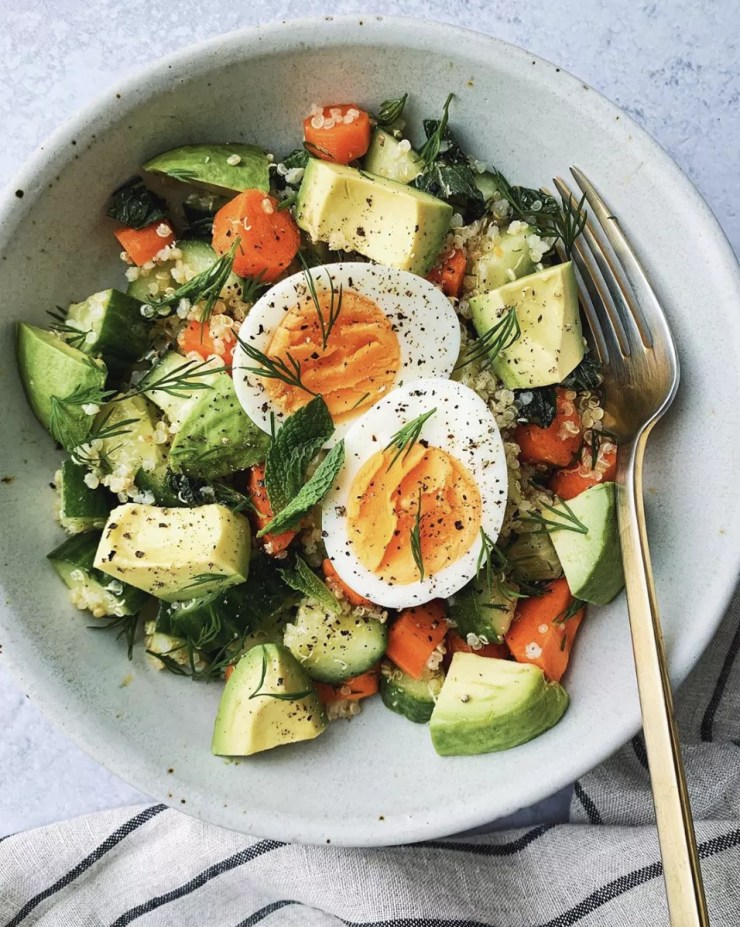 quinoa bowl with avocado, carrots, cucumber, and hard boiled egg