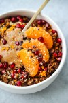 chocolate oatmeal topped with orange slices, pomegranates, and nut butter in bowl