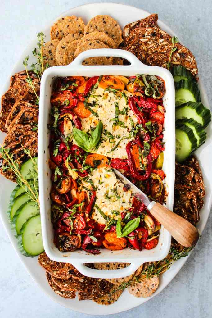 baked feta with peppers and tomatoes in white baking dish