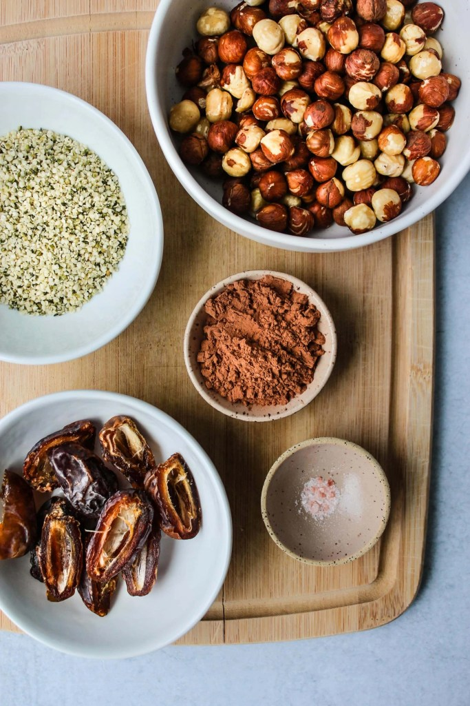 wooden cutting board with bowls of hazelnuts, hemp seeds, cacao powder, dates, and salt