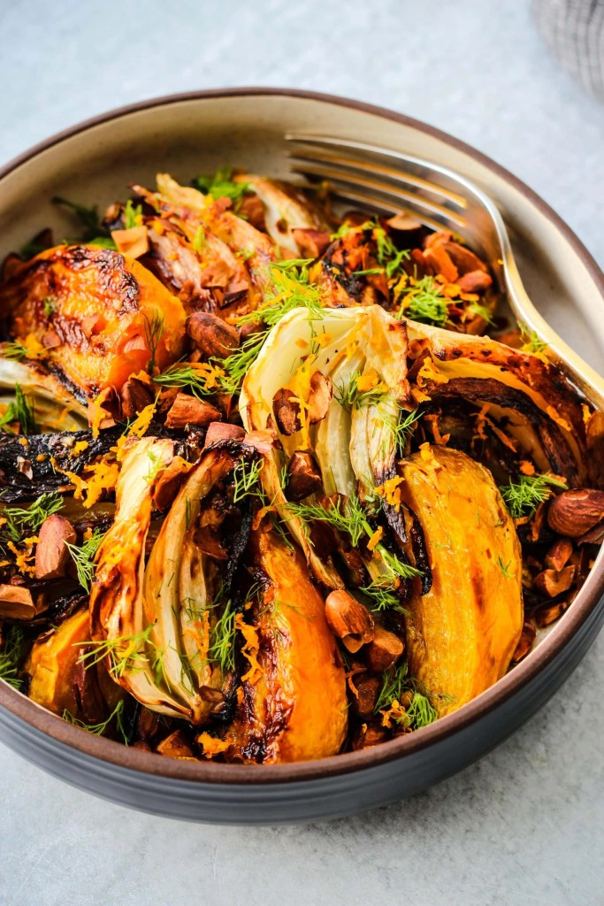 white bowl with roasted beets, fennel, toasted almonds, and orange dressing