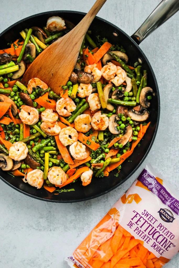 black skillet with sweet potato noodles, shrimp, asparagus, peas