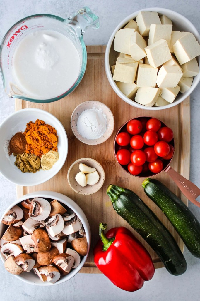 wood cutting board with vegetables and tofu in bowls
