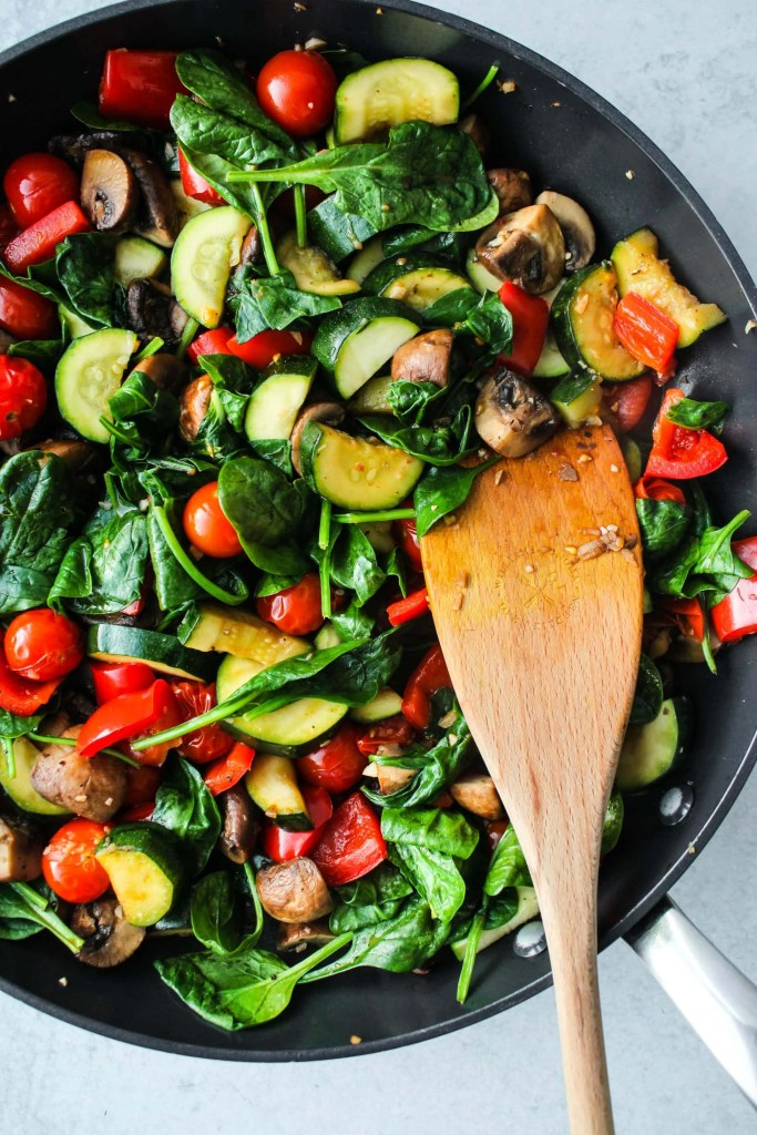 black pan with chopped zucchini, mushrooms, tomatoes, spinach stir fry