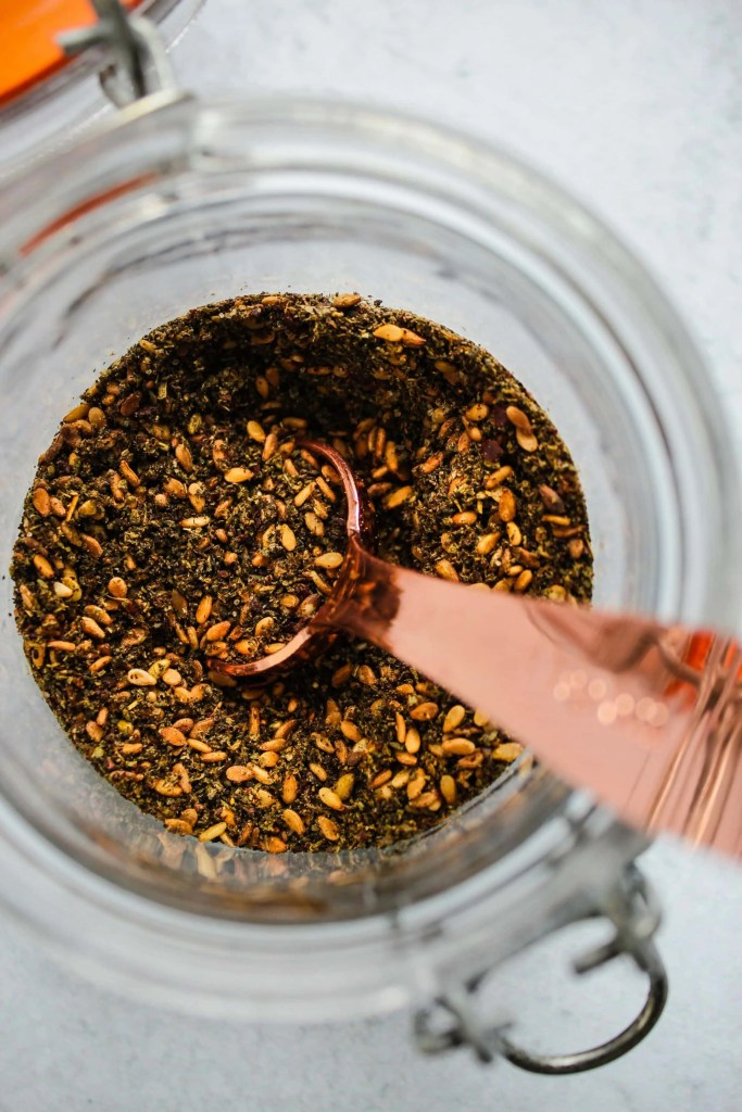 overhead shot of glass jar with za'atar spices, gold spoon