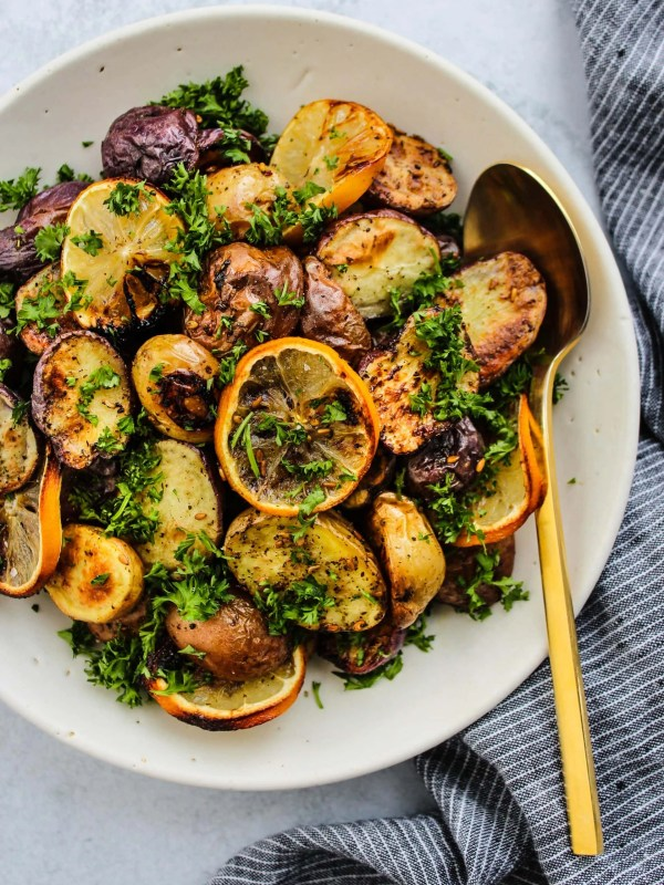 overhead shot of roasted mini potatoes with lemon, za'atar, and parsley in white bowl and gold spoon