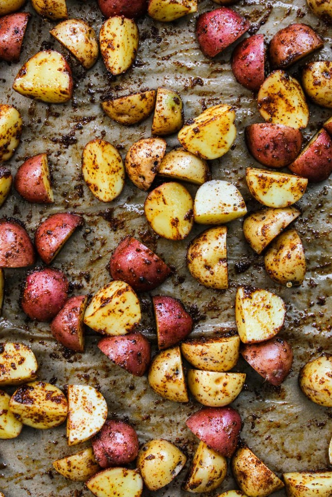 close up of sliced mini potatoes tossed in chili powder and paprika on lined baking sheet