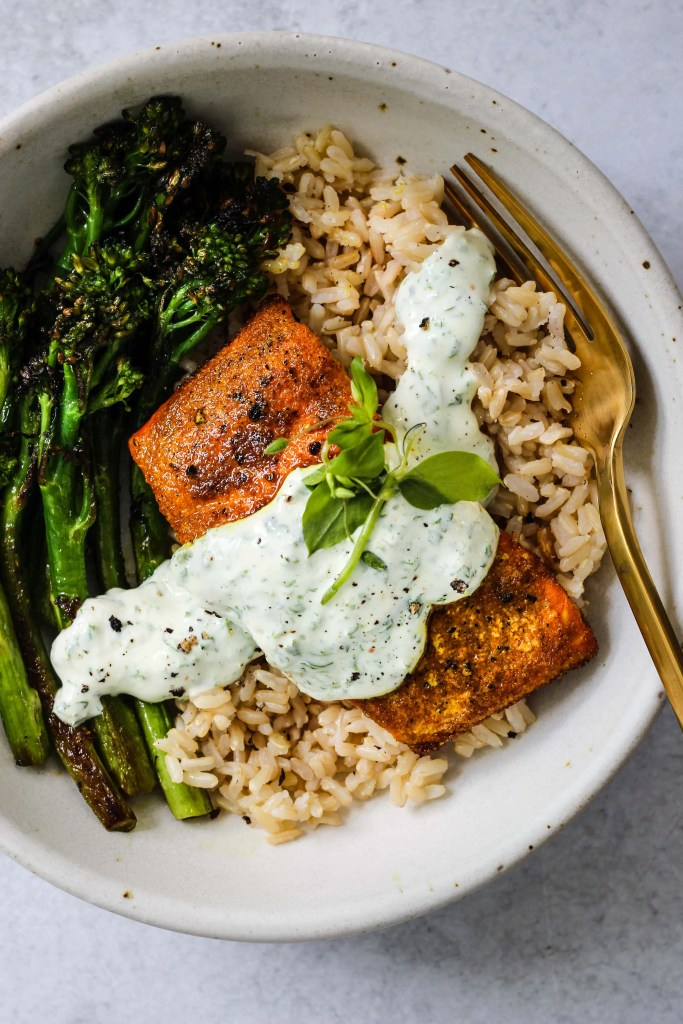 close up of white bowl with broccolini, brown rice, turmeric salmon, parsley yogurt sauce
