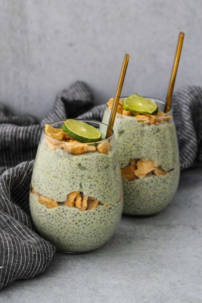 two glass jars with key lime pie chia pudding parfaits and blue towel