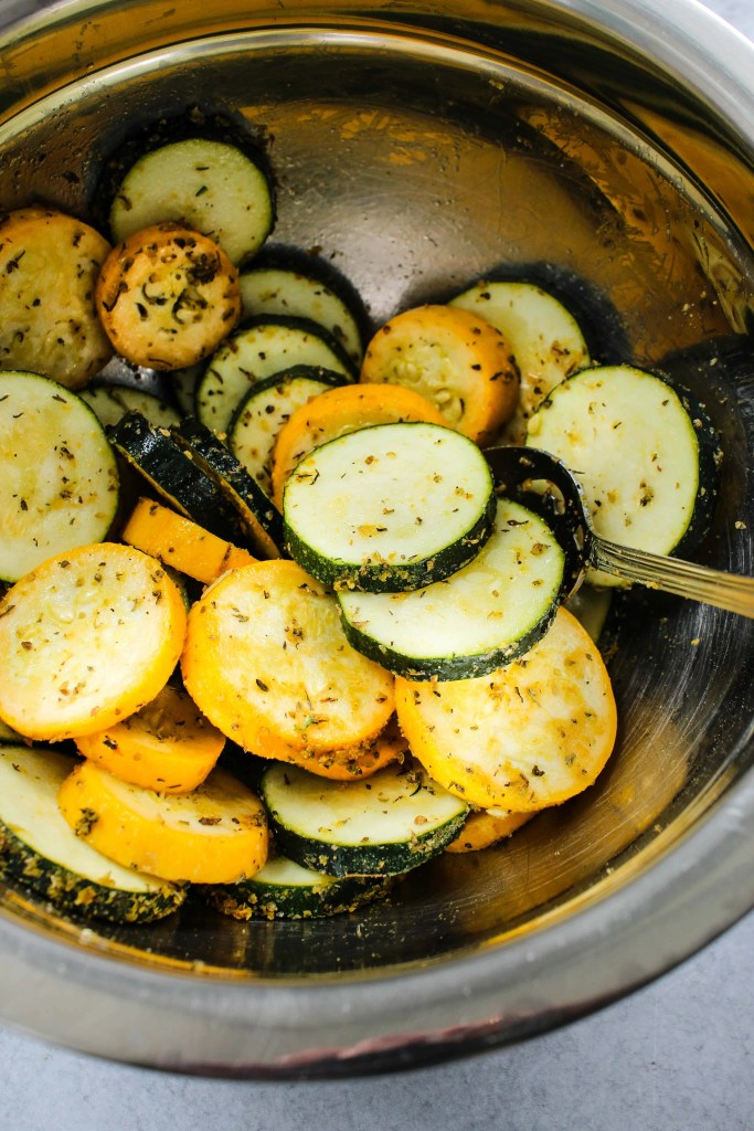 mixing bowl with sliced zucchini rounds and spices