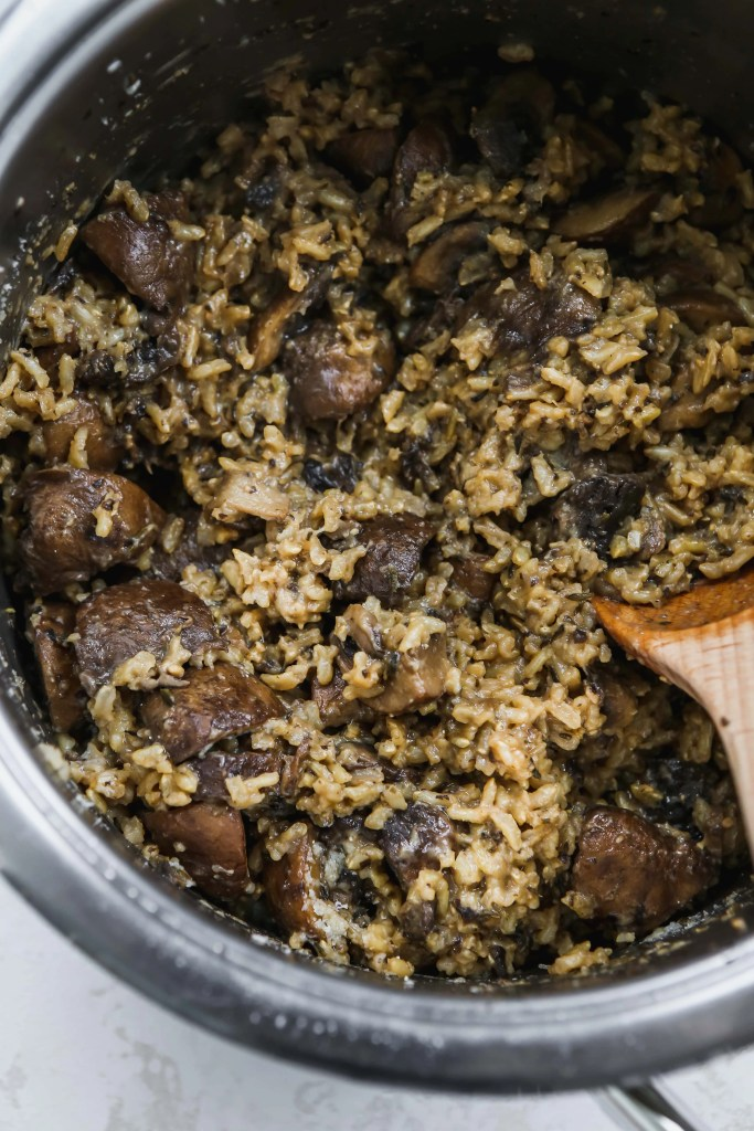 close up photo of large saucepan with a wood spoon stirring brown rice with mushrooms