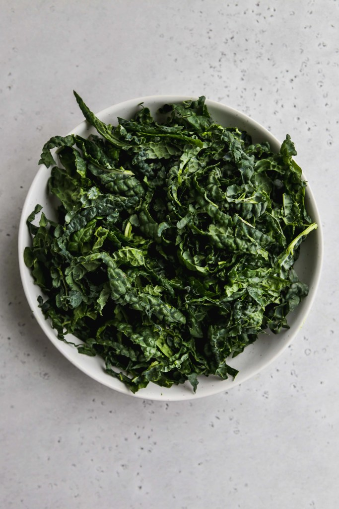overhead photo of white bowl with shredded kale inside