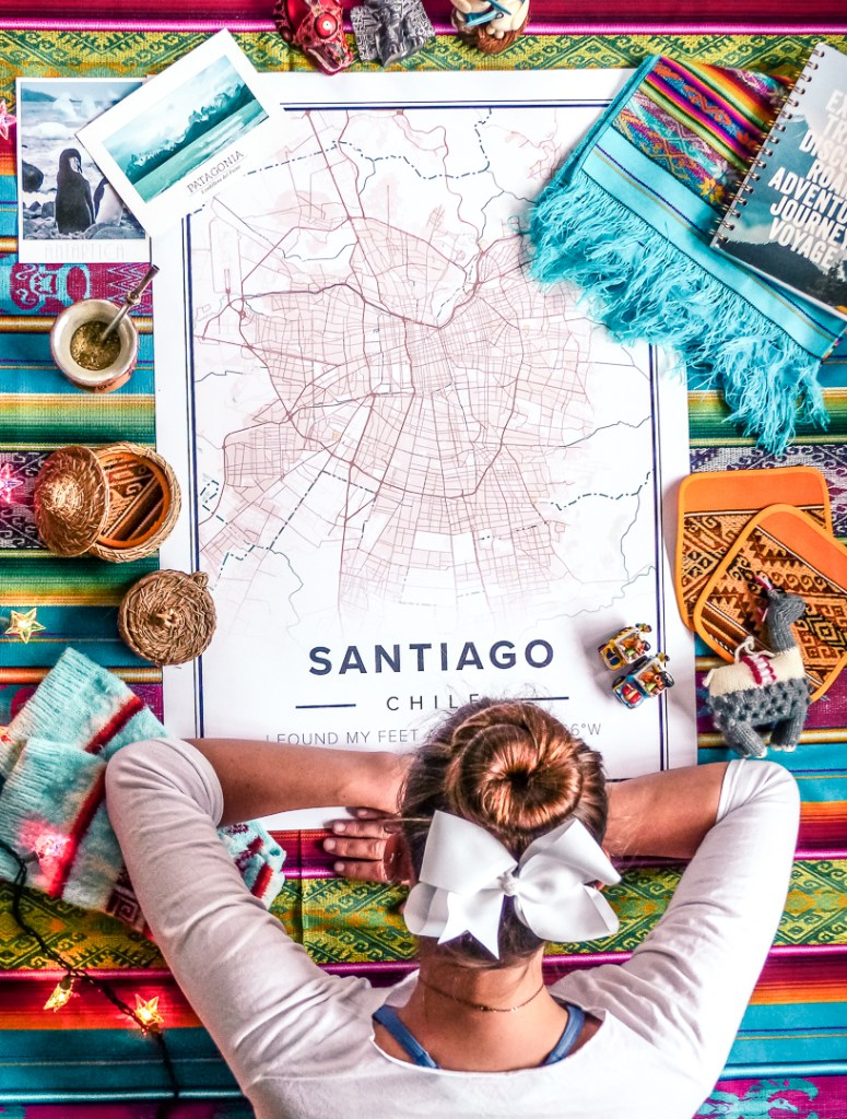 Looking down onto a mapiful picture of Santiago Chile with items from chile all around her