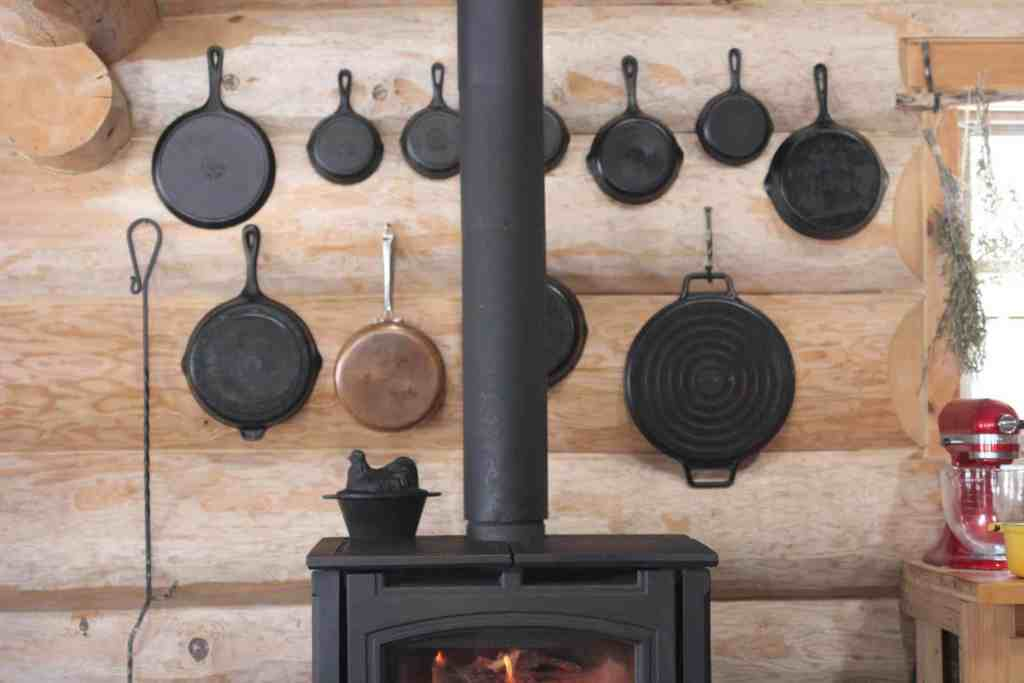Cast iron pans hung behind the wood stove
