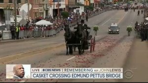 A screenshot of a black funeral carriage drawn by two black horses approaching the Edmund Pettus Bridge.