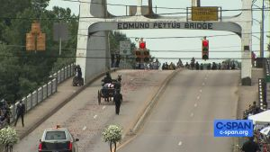 The funeral carriage viewed from behind as it crosses the bridge.