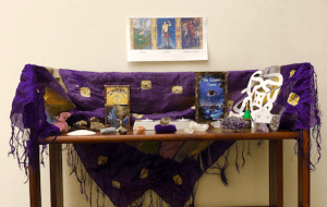 A triptych with images of Sigyn, Loki, and Angrboda on the wall, over an altar draped with a purple cloth with gold shapes and purple fringe, and adorned with various crystals, shells, and candles.