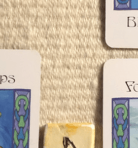 A teaser shot showing just the corners of the cards and one part of a rune from this week's reading.
