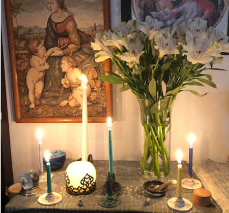 A clear glass vase with white Peruvian Lily flowers stands to the right of the photo. A statue of Kuan Yin is in the center, which holds a lit green candle. There is a tall white candle at the back, and four smaller candles around the edges. At the front are two small silver charms—a money bag and an elephant. There is a small wooden box with a gold leaf moon and two stars on the right, a small bowl and spoon carved from horn near it. A light blue crystal ball on a silver stand is at the left, and a blue glass offering bowl at the back.