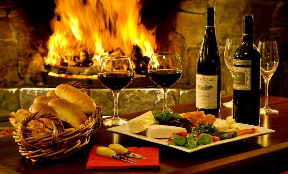A table with a basket of bread, a plate of cheeses and fruits, two wineglasses filled with red wine, two bottles of wine, and two more empty glasses stans in front of a merrily burning fire in a stone fireplace.