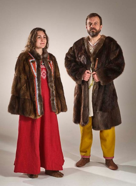 A medium-height woman with brown hair wearing a red linen dress with a white pattern woven into the bodice, leather slipper-style shoes, and a short fur cloak decorated in blue, red, and silver tablet-woven trim stands on the left of the photo. Next to her stands a taller man with short brown hair and a beard, wearing an undyed wool tunic with embroidery, dark yellow long pants edged at the ankles with red tablet-woven trim, and leather shoes. He wears a longer fur coat decorated with tablet-woven bands of wool, which hides most of the embroidery on his tunic.