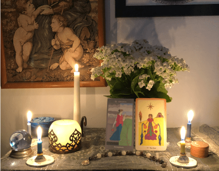 An altar with several lit candles, a bunch of white flowers, and two images of the Goddess Persephone.