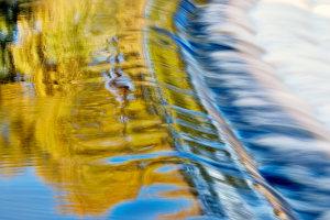 Abstract photo of weir with autumn tree reflections