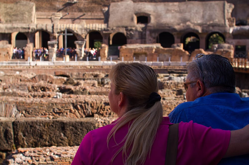 A couple takes in the view inside the Colosseum with a Walks of Italy Tour.