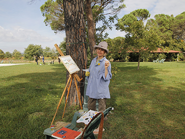 Woman painting in front of an easeal during Walk the Arts art workshops in Italy and painting holidays in Europe
