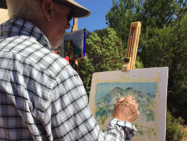 Artist painting in front of an easel during Walk the Arts art workshops in France and painting holidays in Provence
