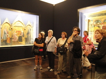 Group of artists of all levels looking at a painting at the Uffizi Museum during our art workshop in Italy