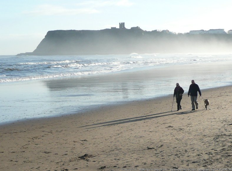Walking the dog on the beach, North Bay, Scarborough The ruined castle keep is silhouetted on the headland