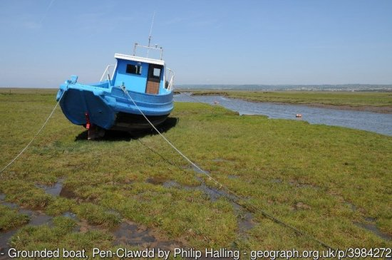 Grounded boat, Pen-Clawdd Grounded boat on the tidal salt marshes at Pen-Clawdd.