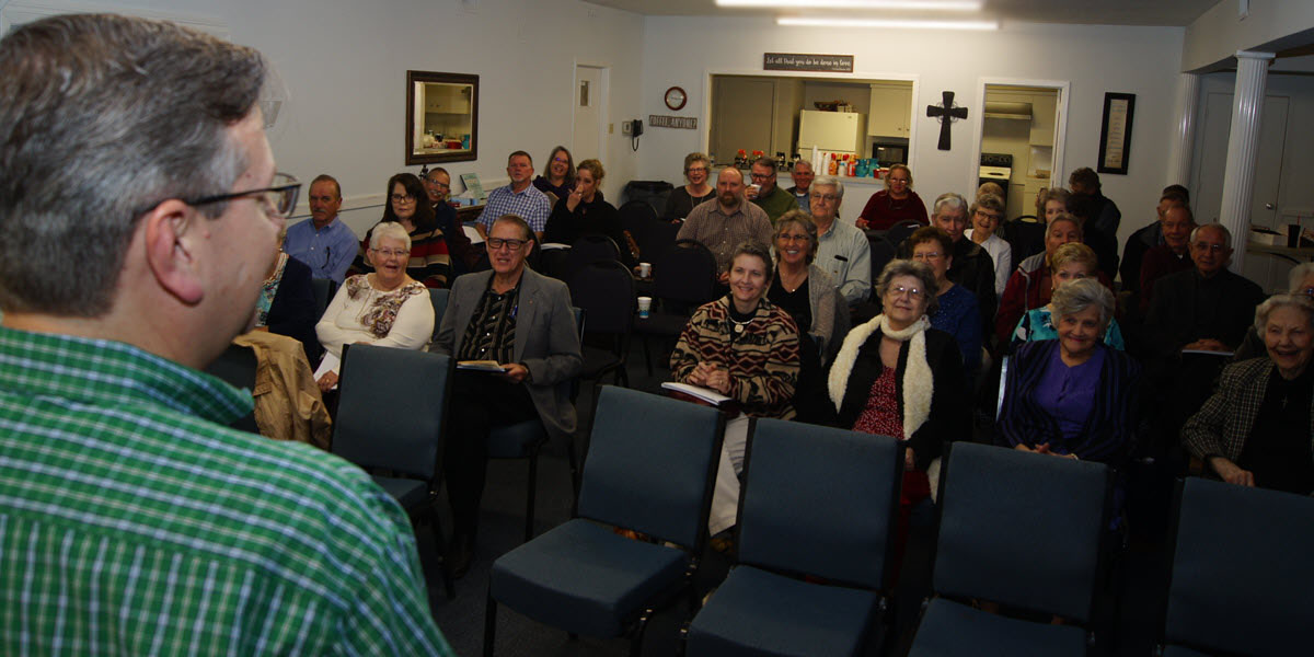 A large group of Adults laughs at a charming Sunday School Teacher