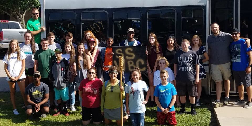A group of adults and teenagers prepare to board a bus to summer Christian camp.