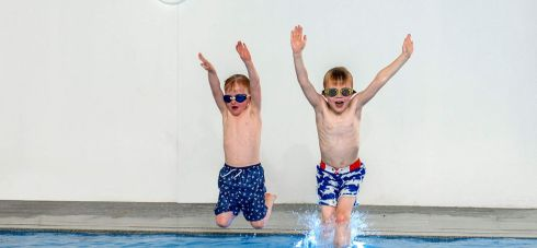 Two small boys jumping into a blue pool