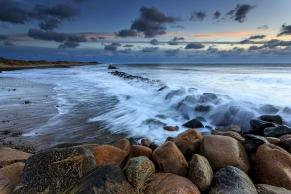 sunset sea beach rocks waves denmark