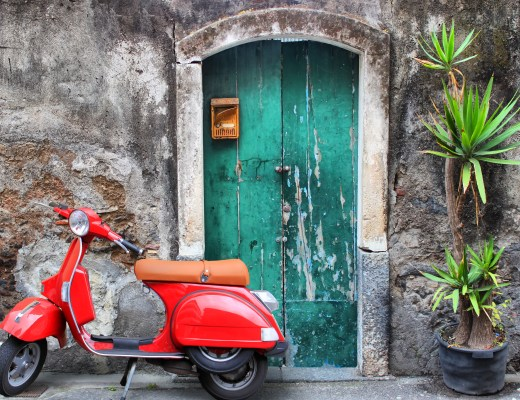 Photo of red scooter near green door and palm