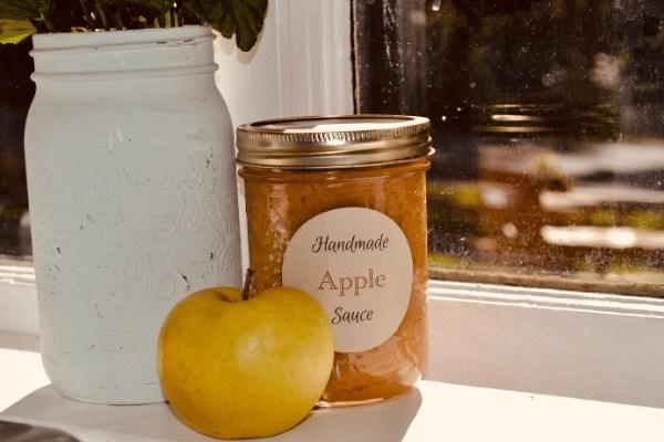 jar of homemade apple sauce sitting on a shelf.