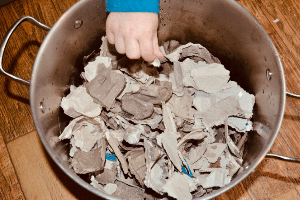 tearing recycling and placing in a large pot for creating seed paper pulp with