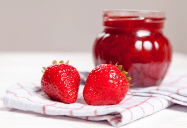 strawberry jam in jar with two strawberries beside on white and red tea towel