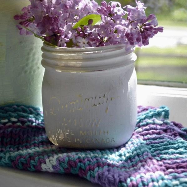 white mason jar with flowers sitting on knitted dishcloth