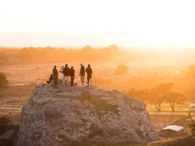 hip campers on a rock looking at sunset