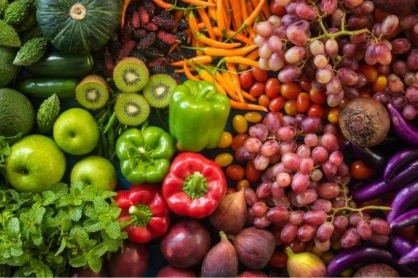 abundance of fruits vegetable and herbs in greens reds oranges and purples