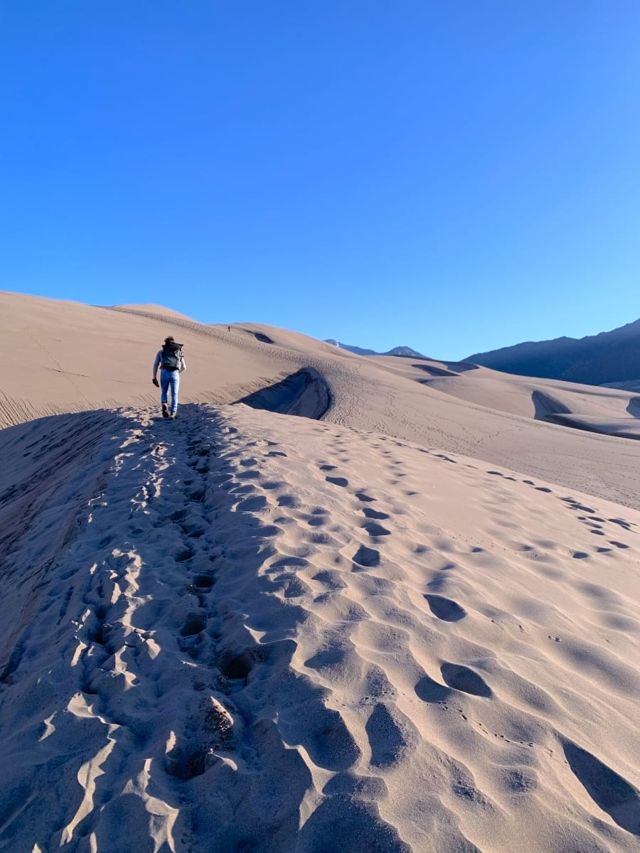 Jesse hiking up the sand dunes