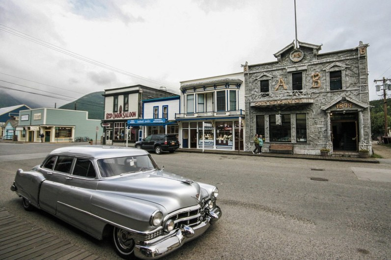 Street view of downtown Skagway stores and an antique car.