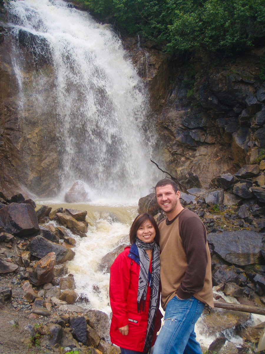 Couple in front of Bridal Veil Falls in the Rocky Mountains near Skagway, Alaska.