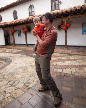 A man dances with his toddler son in a spanish courtyard - Legend of El Dorado in Colombia