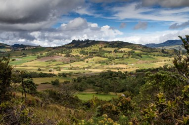 The sun and clouds light up the landscape of mountainside jungles and farm fields - Legend of El Dorado in Colombia