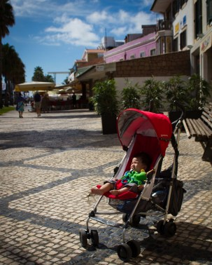 Child sleeps in a stroller in a square - helping kids find nap time on the road